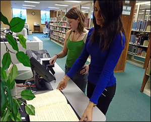 Two students scanning documents in the Library