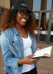 CSUN Student Morgan Cole smiling holding a book
