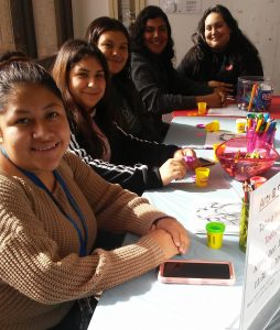 Five CSUN students smiling at Arts & Crafts table