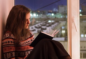 Girl reading a book on a window sill