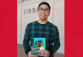 CSUN student Martin Navarro holding book while smiling