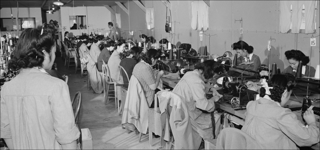 girls working at sewing machines in factory