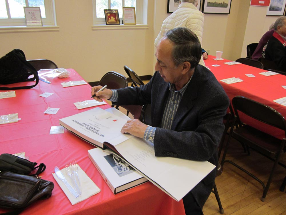 Tony Jorge da Silva inscribes a copy of his book to the Archives