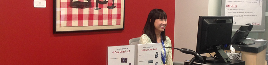 Student Eva Cohen sits at the service desk in the Creative Media Studio
