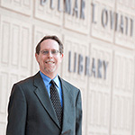 Dean Mark Stover standing in front of the Oviatt Library