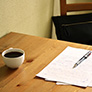 Coffee on a table with paper and a pen