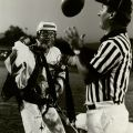 Skydiver Larry Pearlman hands game ball to referee prior to kickoff of home opener, 1981. University Archives Photograph Collection