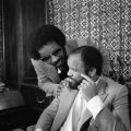 Stevie Wonder leans near to talk with Motown founder Berry Gordy who is siting at his desk in his office. Guy Crowder Collection
