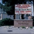 """Cal State Northridge """"Stands"""" sign, with temporary classrooms in background, 1994"""