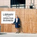 "Library Dean, Susan Curzon, poses next to a sign that reads ""Library is still Open for Business"""