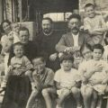 Photograph of family posing with two Catholic priests.