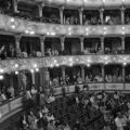 Interior of opera house, with audience in balcony and floor levels
