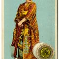 "Katisha, from the Gilbert and Sullivan opera ""Mikado"" wearing a kimono and standing next to a large spool of thread"