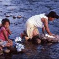 Guatemalan refugees wash clothes in a river, Ixcán, 1983