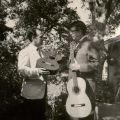 Two men displaying guitars