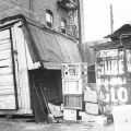 Two makeshift homes sit side by side in an alley. One appears to be an old mobile food truck, and the other a delivery truck. The location is 916 E. 6th St near Skid Row in Downtown Los Angeles.
