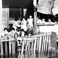 A woman and children on a porch.  This location is now occupied by William Mead Homes public housing project in Chinatown.