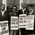Four picketers standing outside the Herald-Examiner Building, 1969 March 29. Paul Kelly, Los Angeles Typographical Union, Local 174 Collection.