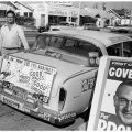 "Campaign associate in front of the ""No on Proposition 18"" campaign car, 1958."