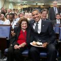 President Barack Obama presents cupcakes with a candle to Hearst White House columnist Helen Thomas in honor of her birthday in the James Brady Briefing Room, on Aug. 4, 2009. Thomas, who turned 89, shares the same birthday as the President, who turned 48. August 4, 2009. By White House (Pete Souza) / Maison Blanche (Pete Souza (Official White House Photostream) [Public domain or Public domain], via Wikimedia Commons
