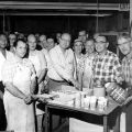 Group portrait at a party at Bendix Corporation plant number one in Hollywood in the machine shop, 1960. Raymond Carter is visible at far left in white shirt