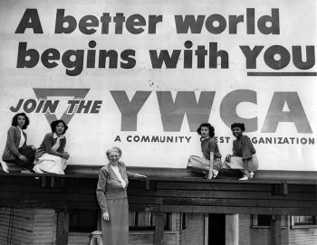 Women standing in front of a YMCA banner
