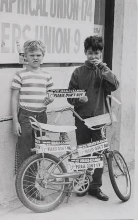 Two boys pose with Herald strike bumper stickers