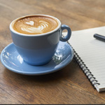Cup of coffee next to a notebook
