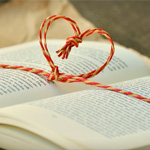 Open book with heart-shaped string across it