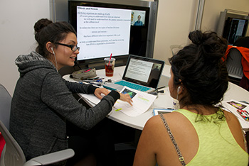 Two students using the shared media table at the oviatt library learning commons