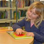 Blonde child touching a page on a book