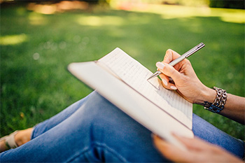 Woman writing in journal outside
