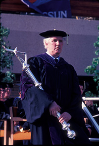 Dean Norman Tanis in academic regalia, mace bearer at a California State University, Northridge (CSUN) commencement ceremony, May 1983
