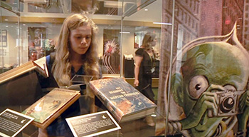 A Young Student Looking at an Exhibition in the Library Gallery