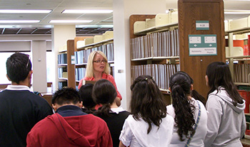 Librarian Coleen Martin giving a tour to outreach students.